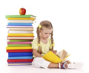 Little girl reading  pile of books. Isolated.